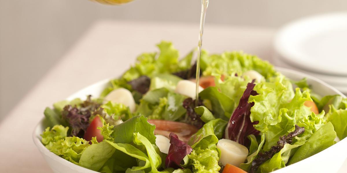 Fotografia em tons de verde e branco de uma bancada de madeira branca com um  recipiente branco quadrado com salada de folhas e um fio de azeite sendo despejado. Ao lado uma tabua de madeira com uma colher de servir.