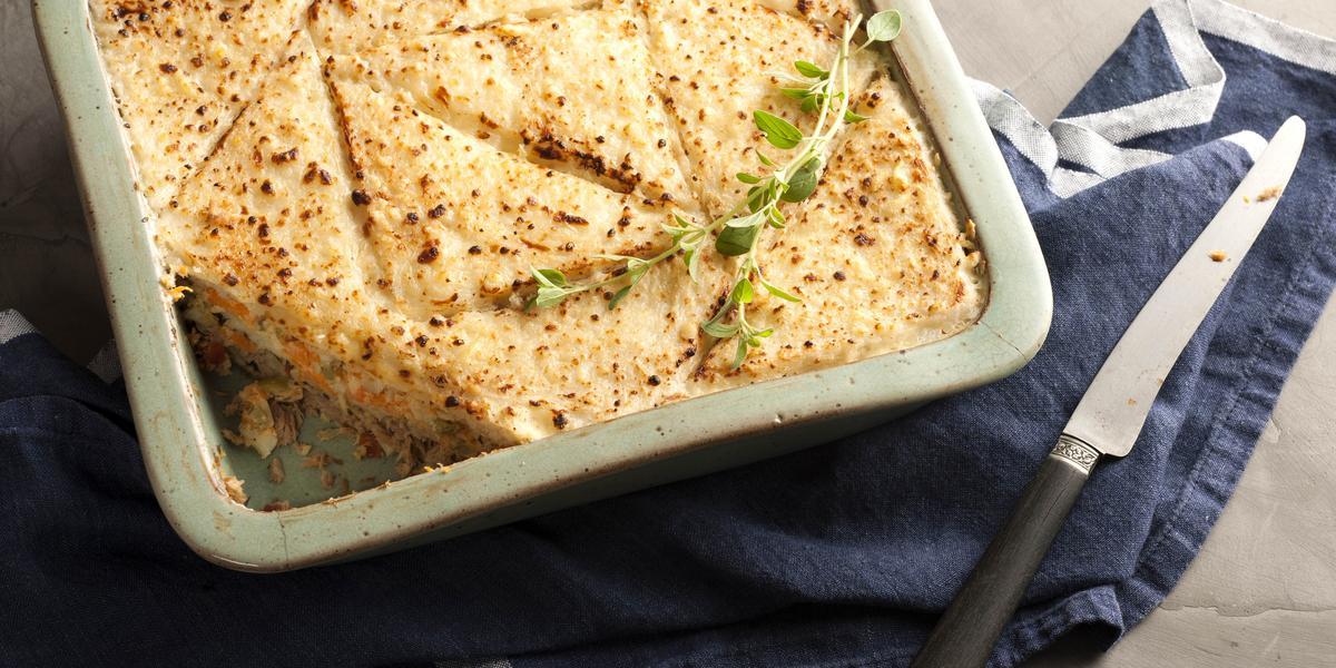 Fotografia em tons de dourado e azul, assadeira com a torta de pão de forma gratinada com queijo e folhas verdes, sobre guardanapo azul com listras brancas, faca ao lado, tudo sobre toalha cinza.