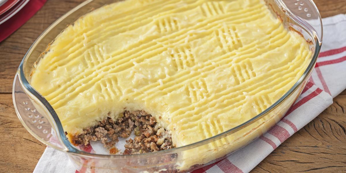 Fotografia em tons de amarelo e branco, ao centro refratário com carne moída e purê de batatas sobre guardanapo branco com listras vermelhas, sobre bancada de madeira.