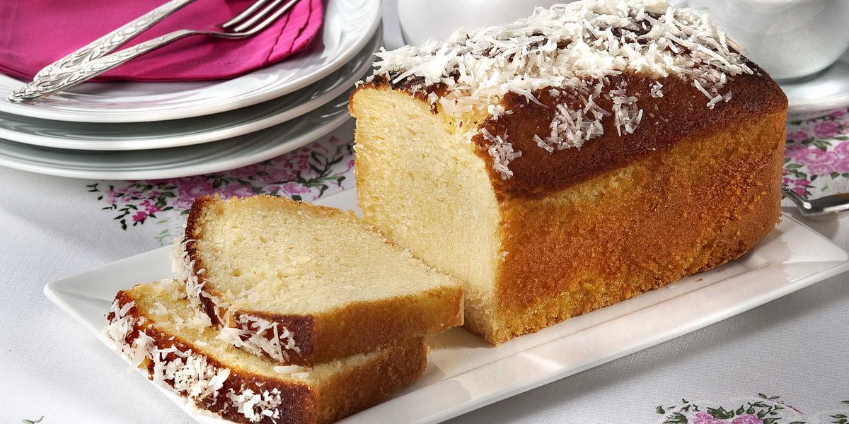 Fotografia em tons de branco de uma bancada branca com um prato retangular com m bolo. Ao fundo pratos brancos com um paninho rosa e garfos. Ao lado uma jarra e uma xícara de chá.