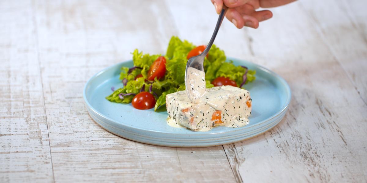 Fotografia em tons de branco e azul de uma bancada branca, sobre ela um prato redondo azul com salão e salada.