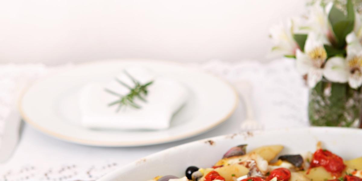 Fotografia em tons de branco e vermelho de uma bancada de madeira vista de lado, ao centro um recipiente oval branco, dentro dele pedaços de bacalhau, tomates cereja e azeitonas. Ao fundo um prato branco e um guardanapo para decorar.