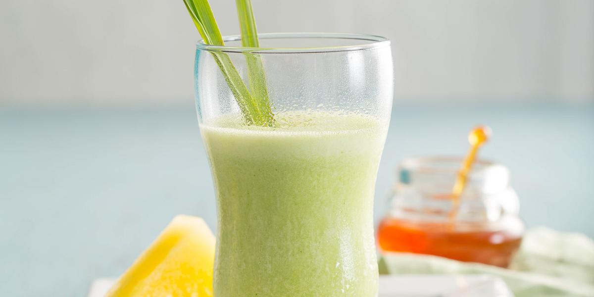 Fotografia em tons de verde em uma mesa de madeira azul clara com um prato retangular branco ao centro com um copo de vidro em cima e o suco de abacaxi, capim-santo e mel dentro dele. Ao fundo, um potinho de vidro com mel.