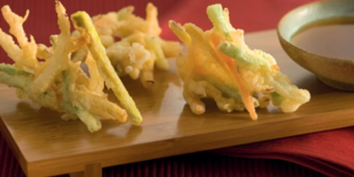 Fotografia em tons de amarelo e vermelho, ao centro uma bandeja de madeira com o tempurá e um potinho com molho ao lado.