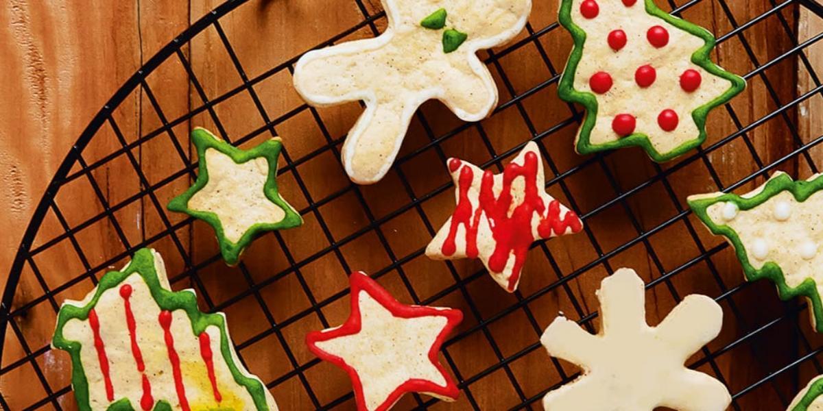Fotografia em tons de marrom e bege, ao centro com biscoitos assados de formas diversas e decorados com glacê, sobre grelha em bancada de madeira.