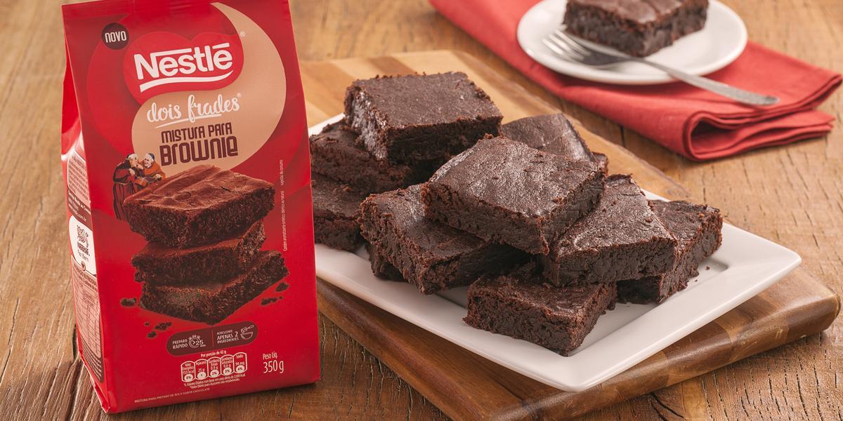 Fotografia em tons de marrom e vermelho de uma bancada de madeira com uma tábua de madeira, sobre ele um papel manteiga com pedaços de brownie. Ao lado a embalagem de brownie dois frades. Ao  fundo um prato com um pedaço de brownie e um garfo.