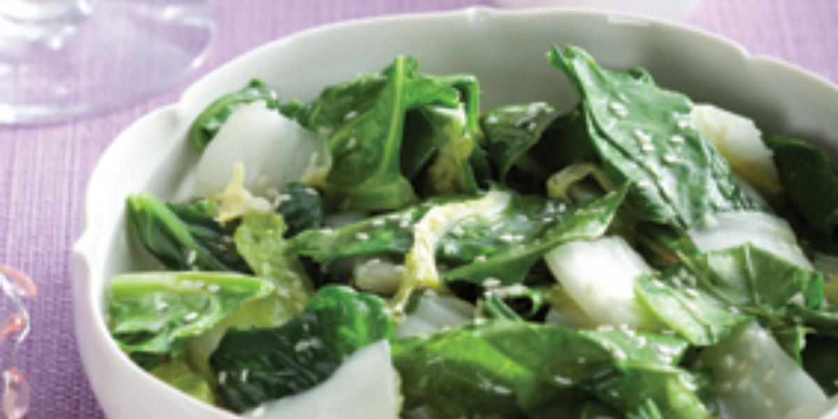 Fotografia em tons de branco, verde e lilás, ao centro uma saladeira com folhas verdes e gergelim, ao lado potinho de azeite, copos e uma jarra, sobre uma toalha lilás,