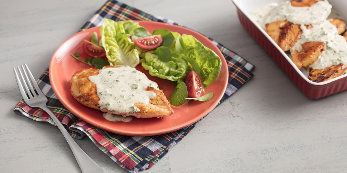 Fotografia em tons de vermelho em uma bancada de madeira cinza com um pano xadrez vermelho, um prato vermelho com o frango com molho de iogurte e ervas e salada dentro dele. Ao lado, um recipiente marrom com mais filés de frango com molho.