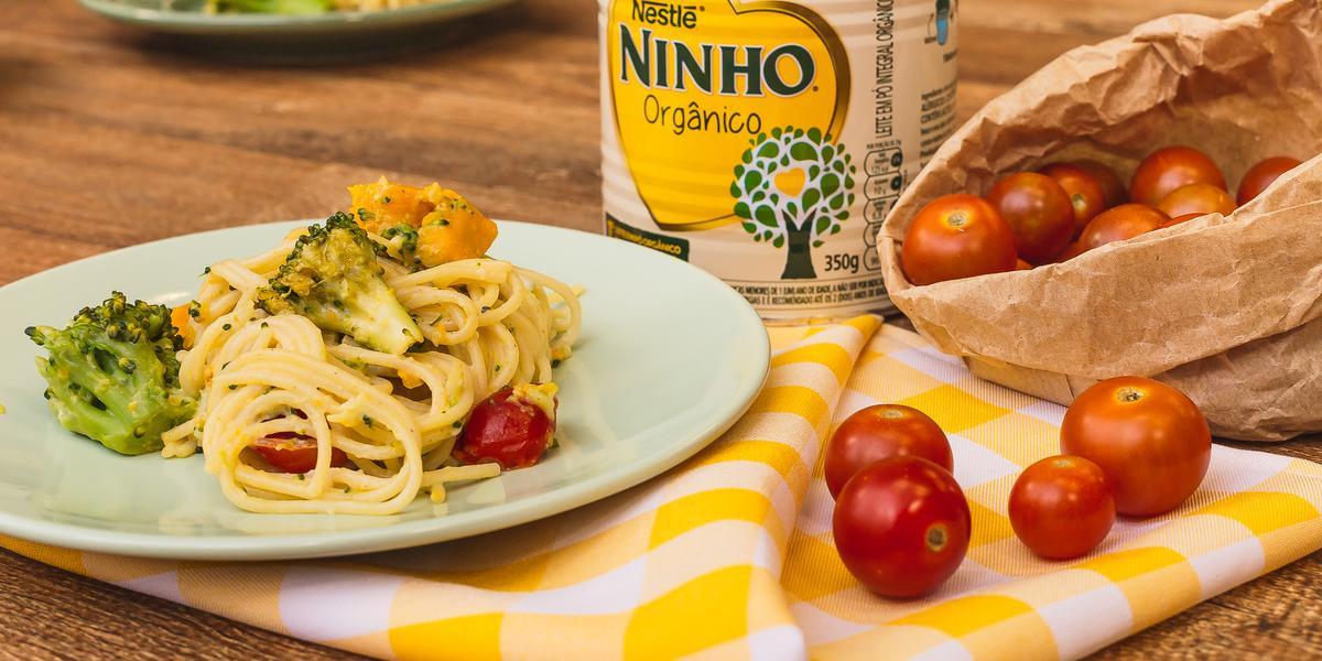 Fotografia em tons de amarelo de uma bancada de madeira com um pano xadrez amarelo e branco de um prato verde claro com o macarrão, brócolis, abóbora e tomate cereja. Ao fundo uma lata de NINHO.