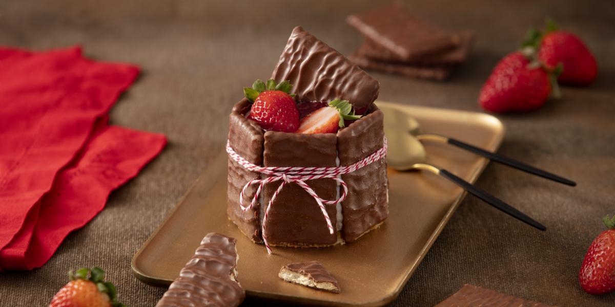 Foto de uma bancada escura com alguns tecidos vermelhos, morangos e biscoitos cobertos de chocolate espalhados. Ao centro há um prato retangular dourado com a receita pronta montada e decorada, acompanhada de duas colheres douradas e pretas