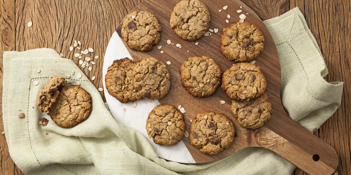Fotografia em tons de marrom e bege, com tábua de cozinha ao centro com cookies assados e sobre guardanapo bege, tudo em bancada de madeira marrom com flocos de aveia espalhados.