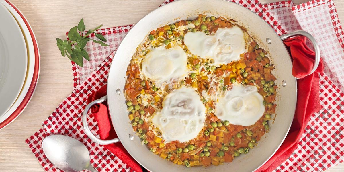 Fotografia em tons de vermelho em uma bancada de madeira clara com um pano de bolinhas vermelhas, uma frigideira de fundo largo com ovos e legumes.