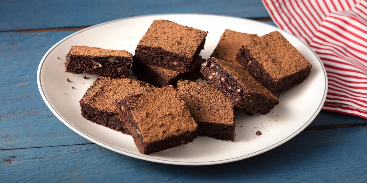 Fotografia em tons de azul, branco e  marrom de uma bancada azul com um prato redondo branco, sobre ele pedaços de brownie de batata-doce. Ao lado um paninho listrado vermelho e branco.