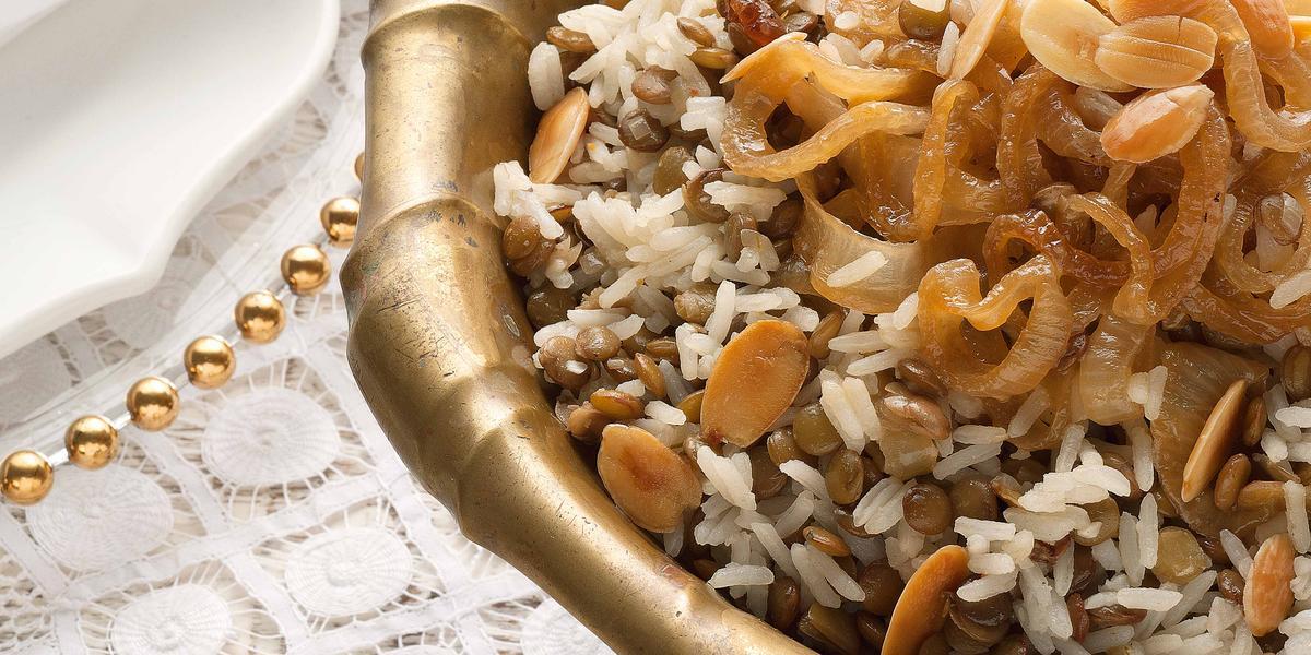 Fotografia em tons de marrom e dourado em uma mesa de madeira com uma toalha branca de renda com um recipiente redondo fundo e grande dourado com o arroz de festa com lentilhas.