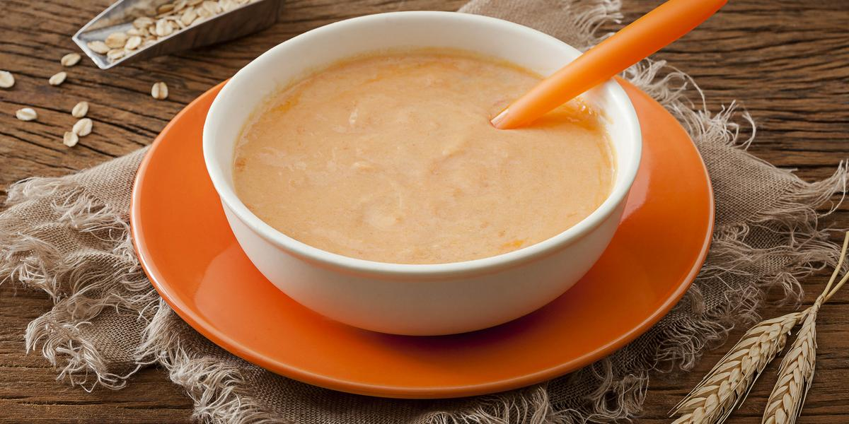 Fotografia em tons de laranja em uma mesa de madeira escura com um pano bege, um prato raso laranja, um prato fundo branco com o creminho de mamão e maracujá dentro dele, com uma colher laranja também dentro do prato.