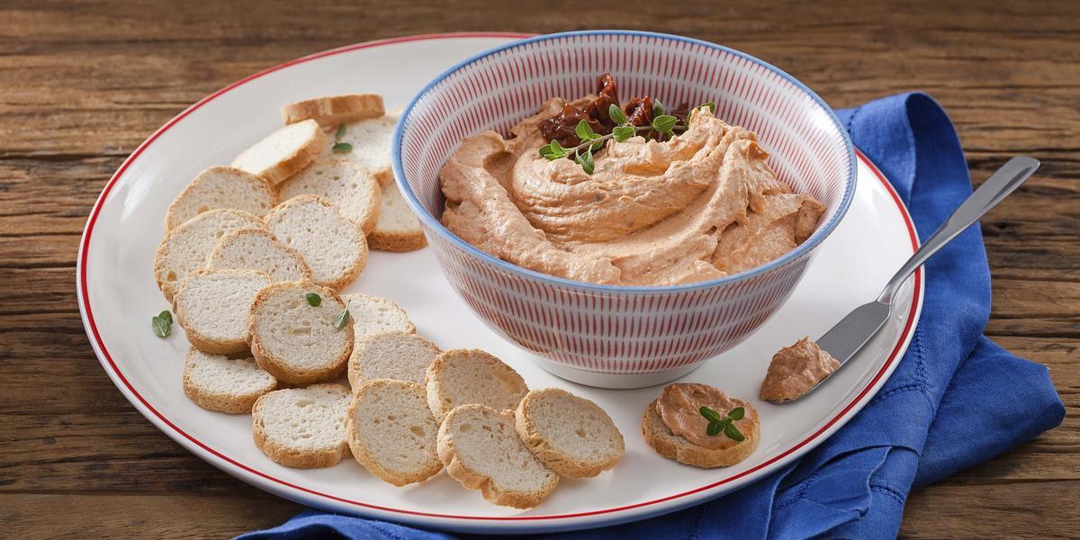 Fotografia em tons de vermelho e azul, ao centro um bowl com o patê e tomates secos para decorar, em baixo está um prato branco com uma faixa vermelha e torradinhas, A direita está um guardanapo de pano azul.
