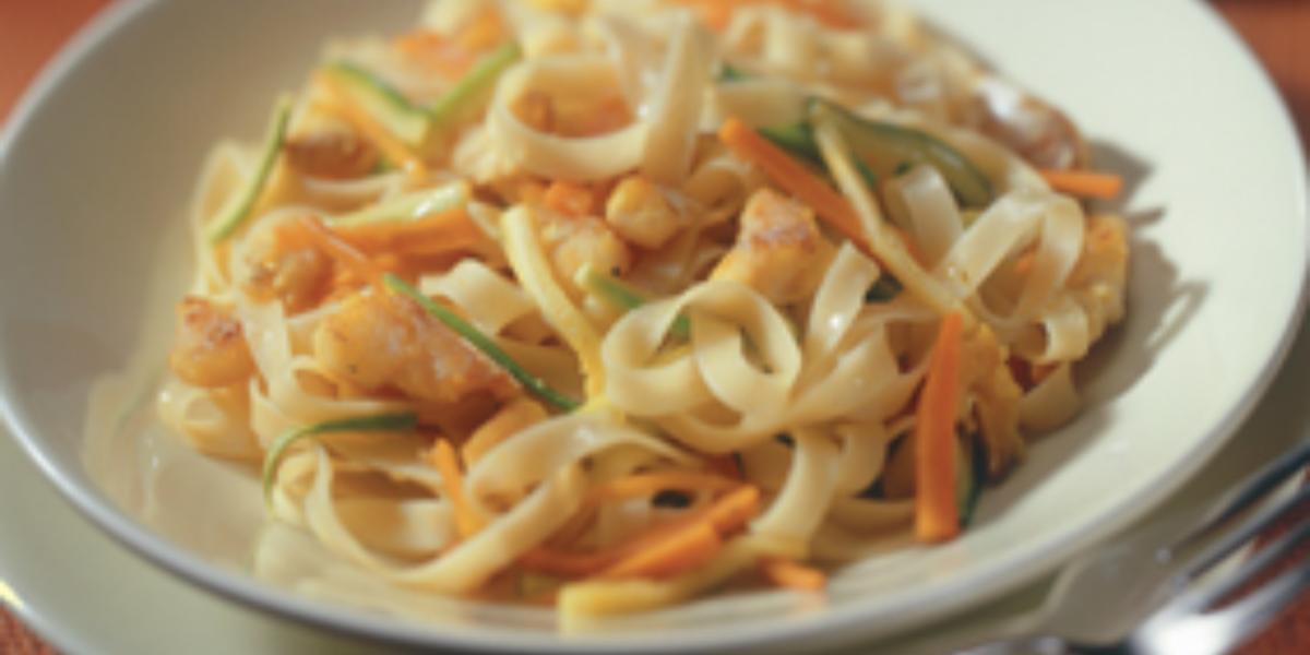 Fotografia em tons de marrom e branco de uma bancada marrom vista de cima, um prato branco com macarrão e cenoura e ao lado um garfo para servir.