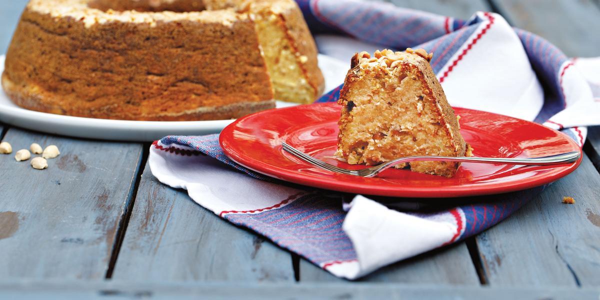 Um prato branco comporta o bolo e um vermelho uma fatia com um garfo. Abaixo um pano nas cores azul e branco.
