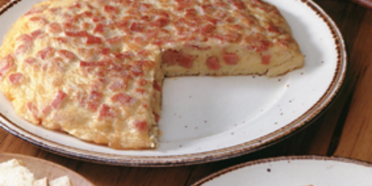 Fotografia em tons de vermelho em uma mesa de madeira com um prato branco raso grande com a omelete cortada ao meio. Ao lado, um prato com a fatia da omelete e outro prato com fatias de pão.