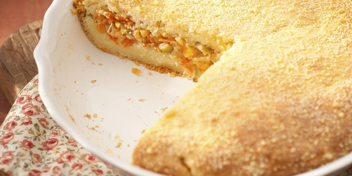 Foto tirada de cima, de uma torta de frango com 2 fatias a menos em um prato branco em cima de um pano estampado com rosinhas