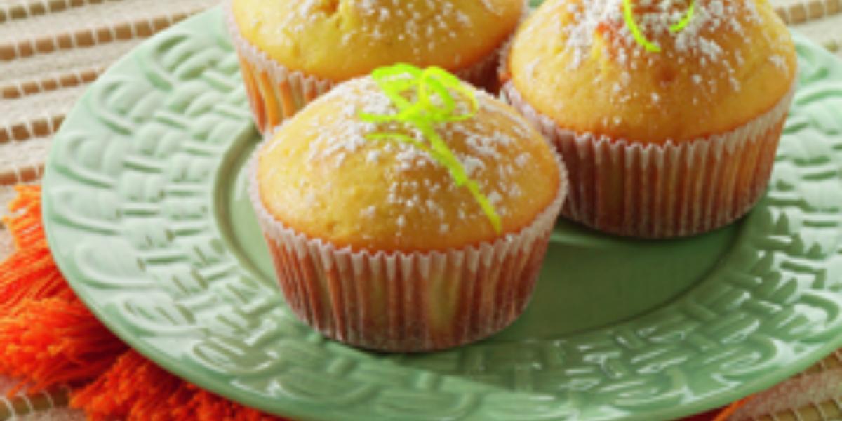 Fotografia em tons de verde, branco e amarelo, ao centro prato verde sobre guardanapo laranja, com três bolinhos decorados com raspas de laranja e açúcar, tudo sobre toalha branca alinhavada.