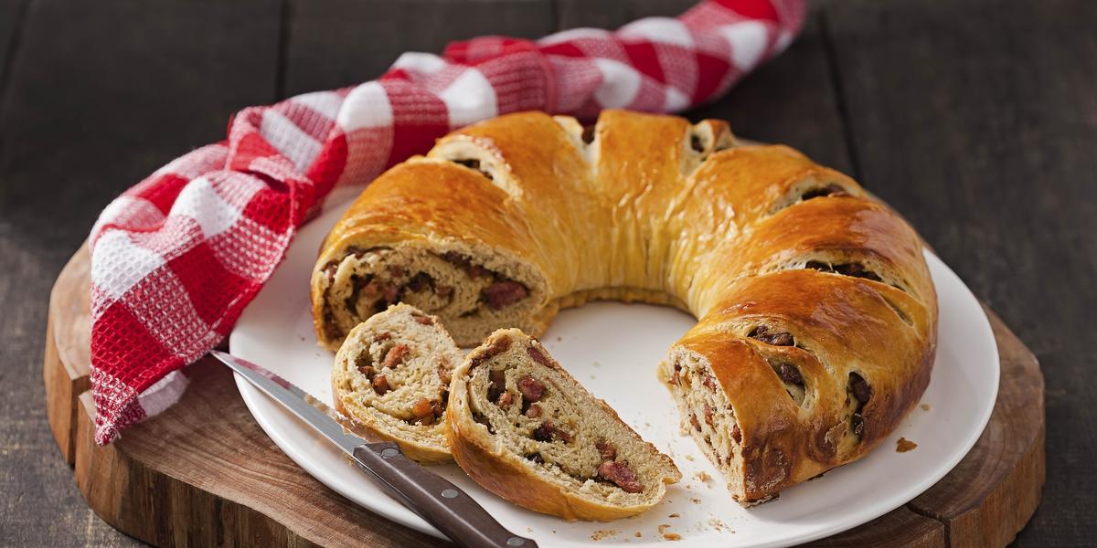 Fotografia em tons de marrom de uma bancada marrom com uma tábua redonda. Sobre ela um prato branco com o pão de linguiça cortado, uma faca e um paninho xadrez branco e vermelho.