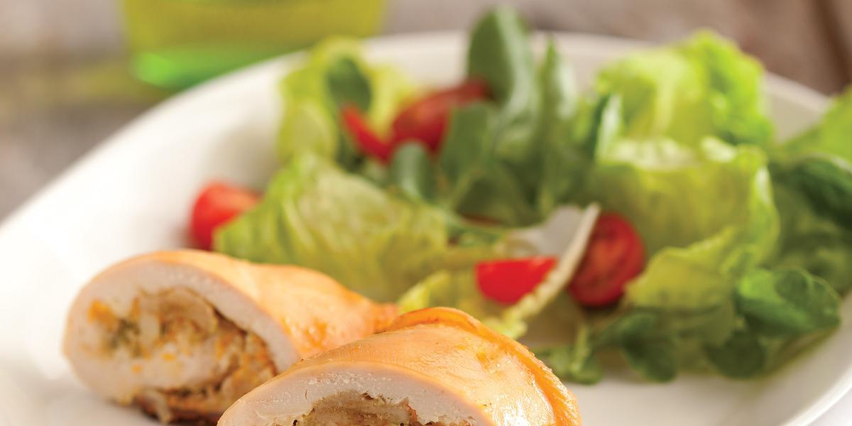 Fotografia em tons de verde em uma bancada de madeira com um prato oval branco com o enroladinho de frango com salada de alface e tomate cereja.