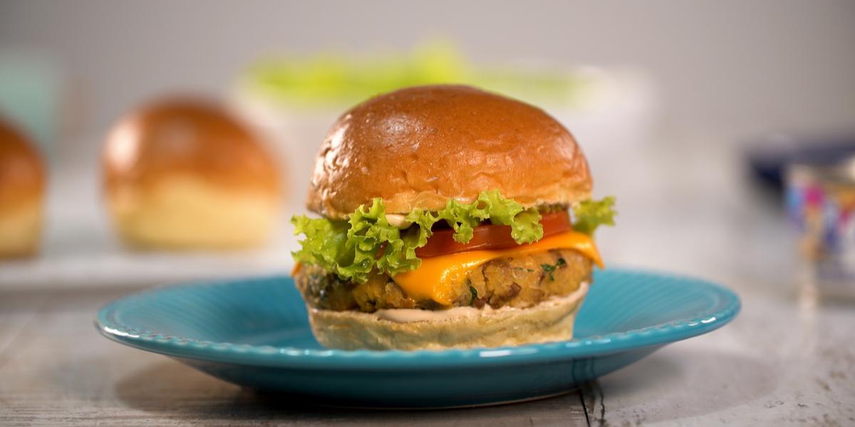 Fotografia em tons de branco e azul de uma bancada branca, sobre ela um prato redondo azul com o hambúrguer.
