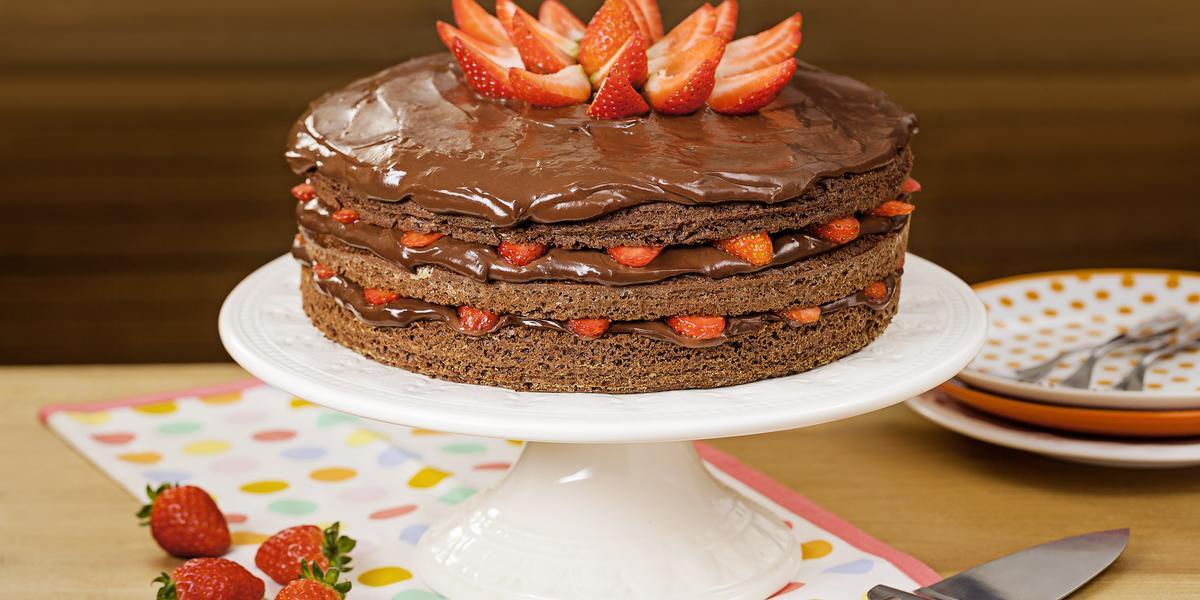 Fotografia em tons de marrom e vermelho de uma bancada de madeira, uma boleira com o bolo de chocolate e morangos. Ao lado quatro morangos para decorar, um espátula para servir e três pratos coloridos em tons de laranja com garfos.