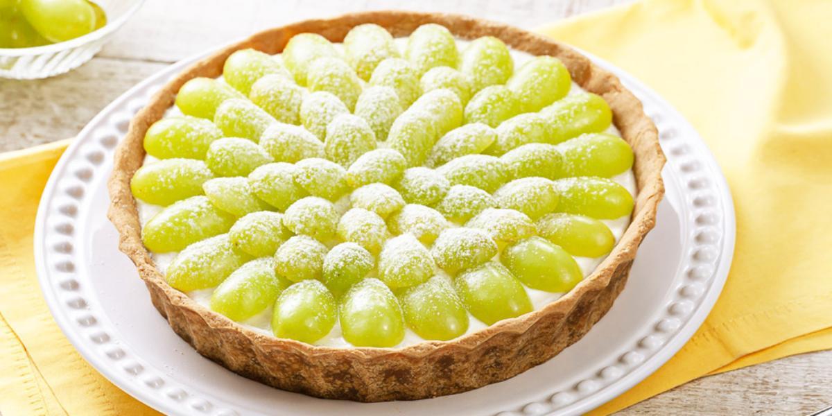 Fotografia em tons de verde e branco, prato branco ao centro contendo uma torta de uva sobre guardanapo amarelo, ao lado potinho com uvas, tudo sobre bancada de madeira com tons em branco