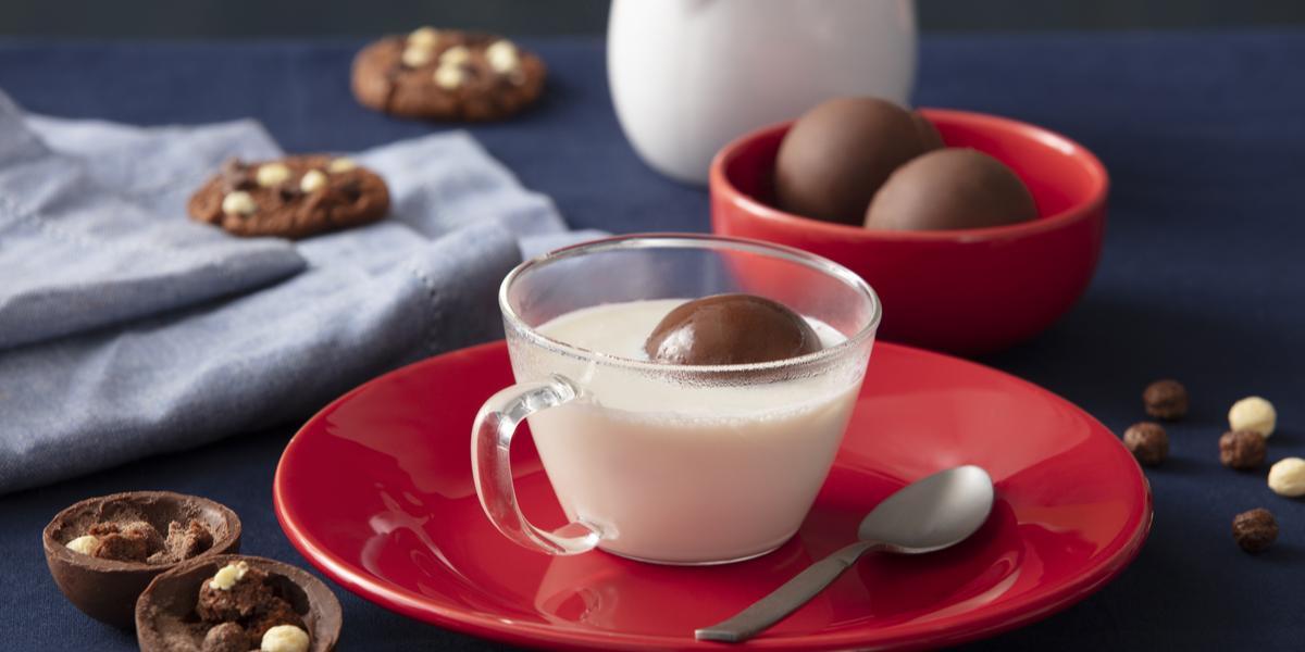 Foto de uma bancada escura. No centro há um prato vermelho com uma xícara com leite no centro e, dentro dela, há uma esfera de chocolate boiando. Ao lado do prato há mais algumas esferas fechadas, uma aberta, alguns cookies e cereal espalhado