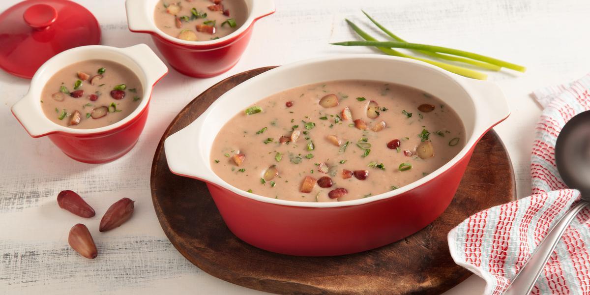 Fotografia em tons de branco e vermelho de uma bancada vista de cima. Em cima de uma tábua redonda contém um recipiente oval com alças nas cores vermelho e branco com a sopa e pedaços de pinhão por cima, ao lado dois potinhos com a sopa e um pano