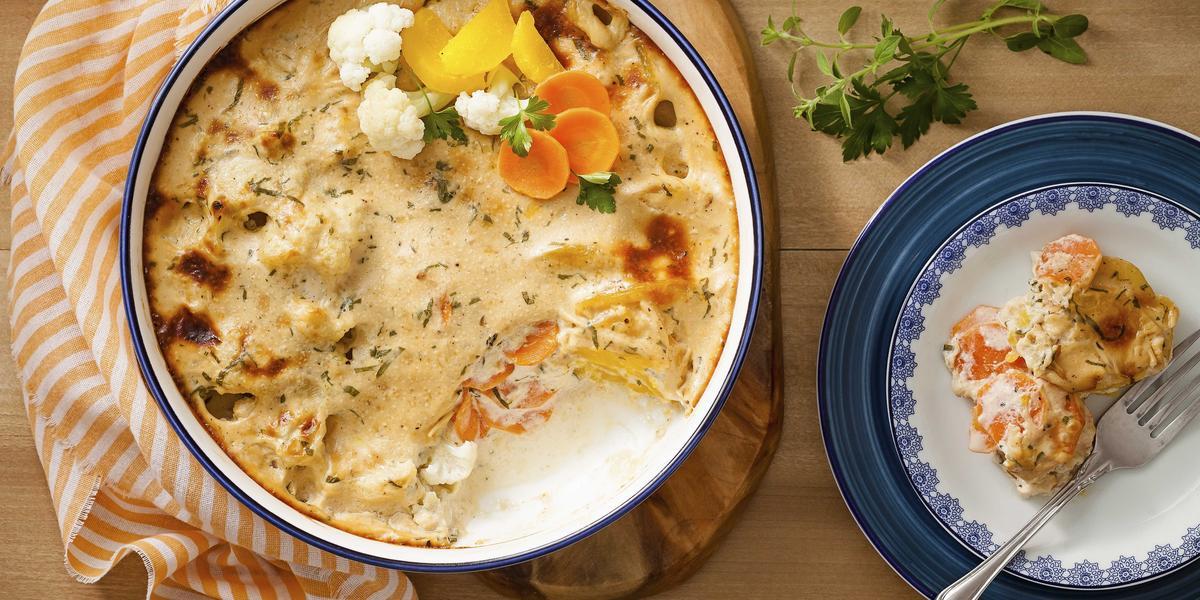 Fotografia em tons de laranja e azul em uma bancada de madeira com um pano com listras laranjas, uma tábua de madeira com um refratário grande e redondo com legumes gratinados. Ao lado, um prato branco com detalhes azuis, com um pedaço dos legumes.