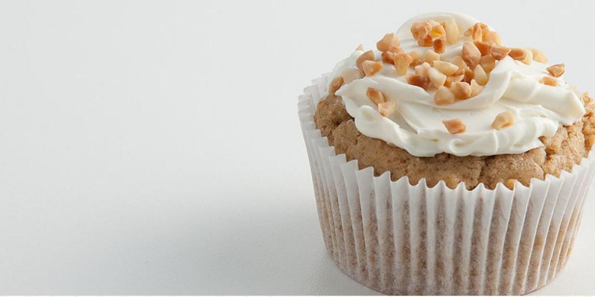 Fotografia em tons de bege em uma mesa branca com uma forminha de doce grande branca com o cupcake de massa integral dentro dele. Decorado com castanhas-de-caju.