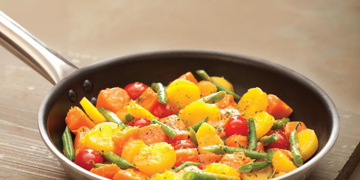 Fotografia em tons de amarelo e marrom, com frigideira ao centro com legumes salteados e sobre tábua de cozinha marrom, tudo sobre bancada em tom de marrom.