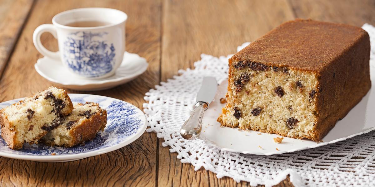 Fotografia em tons de marrom e branco de uma bancada marrom com um prato branco, sobre ele um bolo. Ao lado um prato pequeno redondo com uma fatia de bolo e uma xícara de chá.