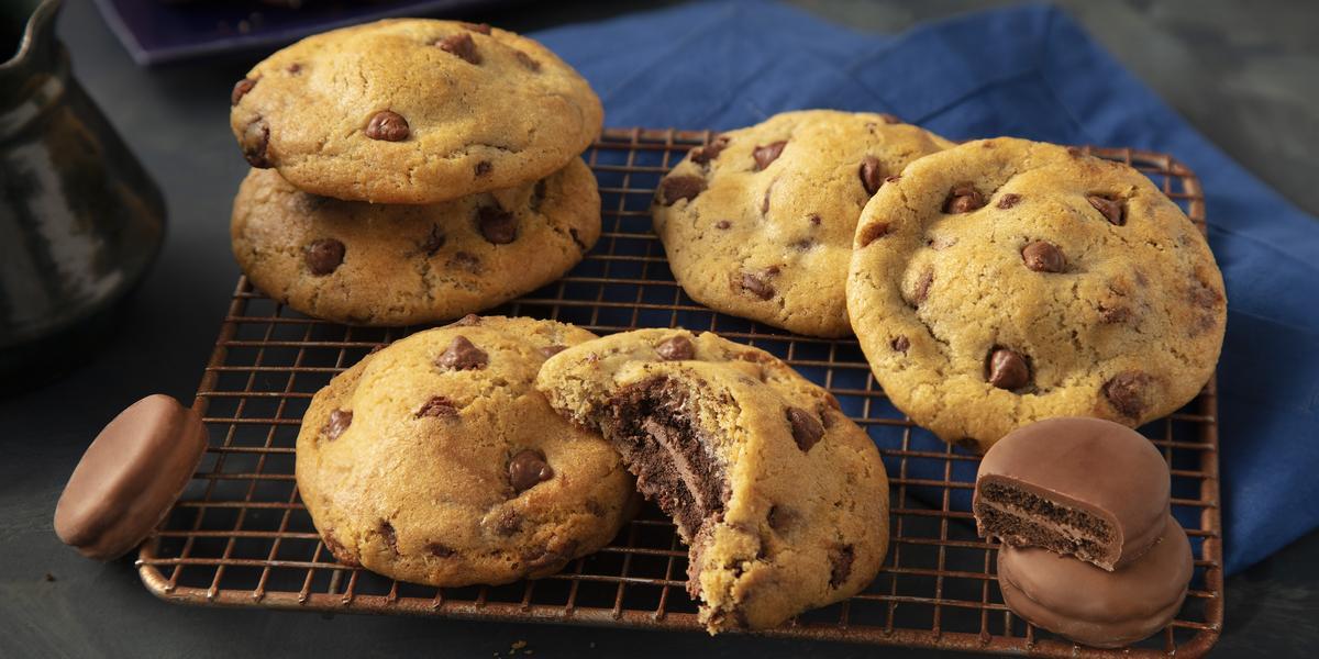 Fotografia em tons de preto e azul de uma bancada preta com um grade dourada, sobre ela cookies. Ao fundo um paninho azul e biscoitos negresco cobertos de chocolate espalhados.