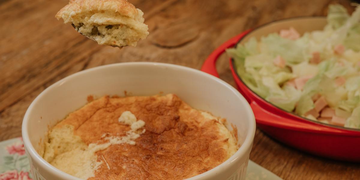 Fotografia em tons de marrom e vermelho de uma bancada de madeira com um paninho azul florido, sobre ele um recipiente refratário redondo e branco com o suflê. Ao fundo um recipiente com uma salada de alface.