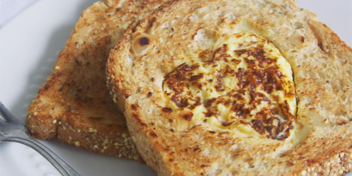 Fotografia em tons de bege em uma mesa de madeira clara com um prato branco raso e duas fatias de pão integral com a omelete dentro dele.
