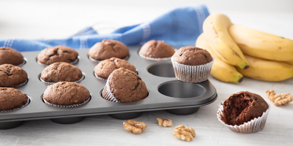 Fotografia em tons de cinza, marrom e amarelo, forma com cupcakes de chocolate em bancada cinza, nozes espalhadas ao redor, ao lado um cacho de banana e um cupcake aberto e ao fundo um guardanapo azul com listras brancas.