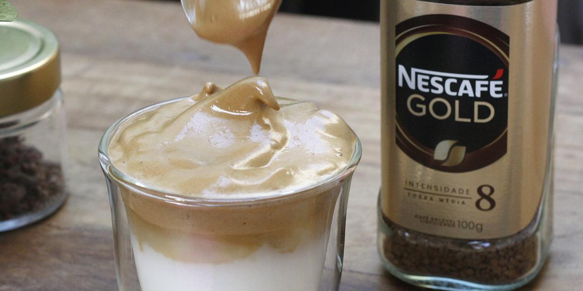 Fotografia em tons de marrom de uma bancada de madeira, sobre ela um copo de vidro com o dalgona coffé e uma colher. Ao lado um recipiente do Nescafé gold.