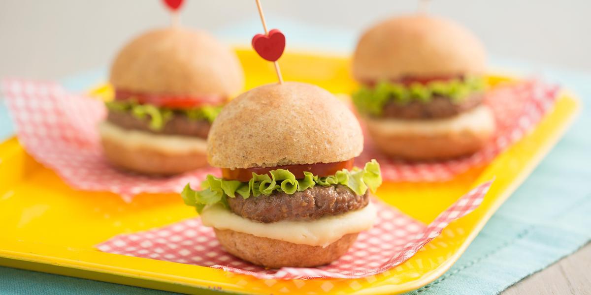3 mini hambúrguer por cima de uma bandeja amarela. Abaixo um pano azul claro. Fotografia tirada de frente de uma bancada cinza.