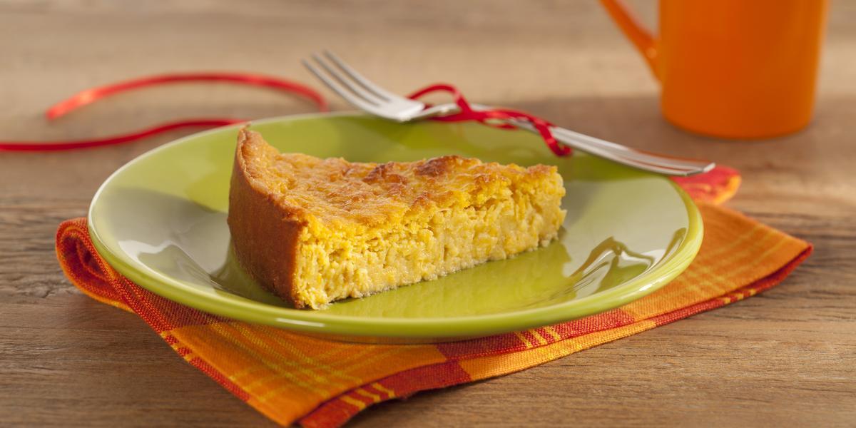 Em uma mesa contém um pano em tons laranja e vermelho, por cima, um prato na cor verde que comporta uma fatia de bolo. Ao lado do prato um garfo de metal e uma xicara laranja.
