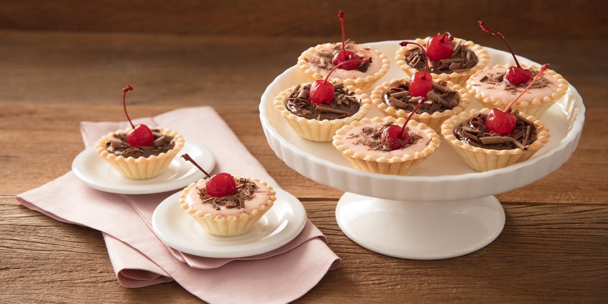 Fotografia em tons de vermelho em uma bancada de madeira, um paninho rosa, um suporte para bolo branco com várias tortinhas de Moça com cerejas para enfeitar. Ao lado, dois pratinhos brancos pequenos cada um com uma tortinha em cima.