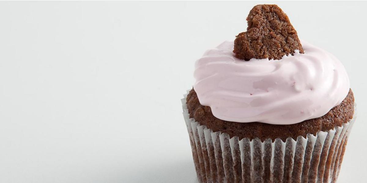 Fotografia em tons de branco, marrom e rosa vista de frente. Contém um bolinho de chocolate com creme de cereja e para decorar um mini bolinho em formato de coração por cima.