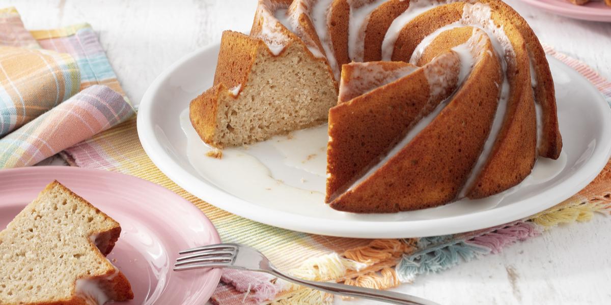 Fotografia em tons de branco e rosa de uma bancada branca com um paninho colorido, sobre ele um prato branco redondo com um bolo. A frente um prato redondo rosa com uma fatia de bolo e um garfo.