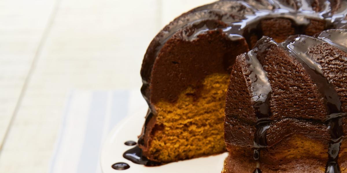Fotografia em tons de marrom em uma bancada de madeira com um pano branco com listras azuis. Ao centro, um prato branco redondo raso com uma fatia do bolo de cenoura com chocolate. Ao fundo, um suporte branco para bolos com o bolo inteiro.