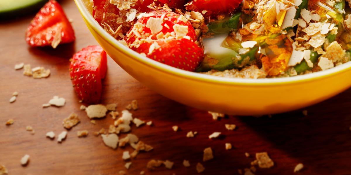 Fotografia em tons de vermelho em uma bancada de madeira escura, um potinho amarelo com as frutas e com os cereais Neston em cima delas e dentro do potinho. Ao fundo, um potinho de vidro com mel.