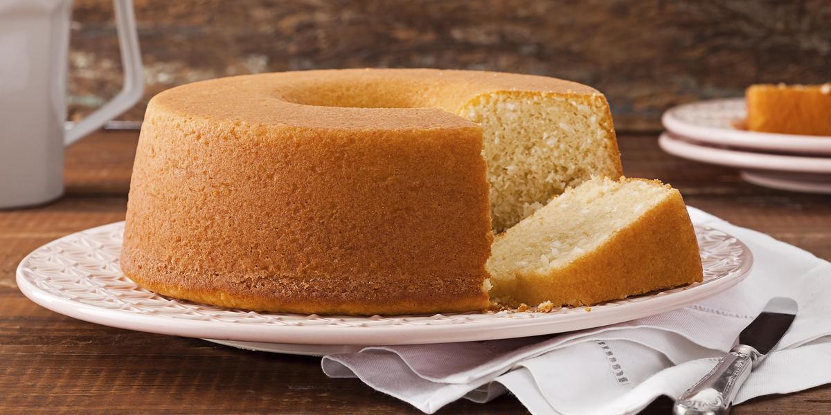 Fotografia em tons de marrom, laranja e branco de uma bancada marrom vista de frente, um prato branco contém um bolo com uma fatia cortada ao lado e abaixo e um pano branco. Ao fundo dois pratos brancos com uma fatia por cima e uma jarra branca.