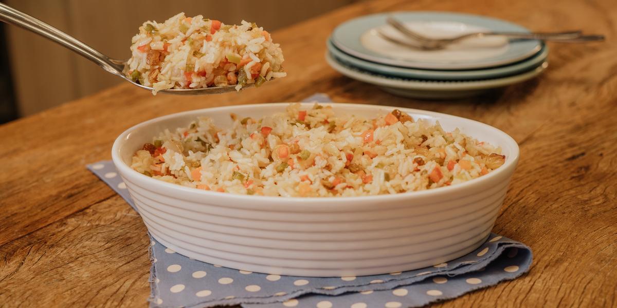 Fotografia em tons marrons com fundo de madeira com paninho azul de bolinhas brancas, ao centro um recipiente branco oval com o arroz a grega e uma colher com uma porção do arroz, ao fundo três pratos pequenos com um garfo.